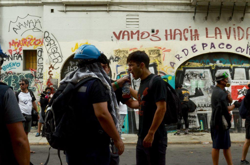 Cuadro de texto: Observadores de los derechos humanos ayudan a manifestante en Plaza Dignidad tras ser víctima de los gases lacrimógenos, enero 2020.
